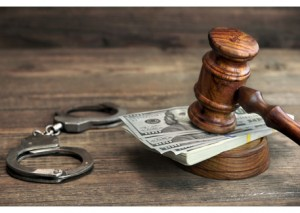 Dollar Banknotes, Handcuffs And Judge Gavel On Wood Table
